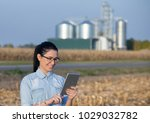 Small photo of Pretty young woman holding tablet in field with grain silos in background. Agribusiness concept