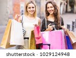 laughing girls carrying bags... | Shutterstock . vector #1029124948