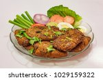 Small photo of Tasty Indian Bengali starter dish of crispy bhetki fish fry garnished with beans and egg slice with carrot tomato and onion.