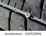 screw puncturing tire - stock photo