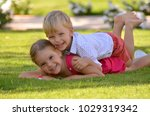 Small photo of Brother and sister hugging and playing on grass in a park on a summer sunny day