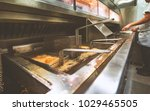 chips cooking in fish and chip... | Shutterstock . vector #1029465505