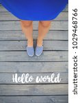 Small photo of girl's legs stand in a blue dress on a wooden bridge-inscription hello world