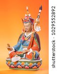 Small photo of Figurine of Padmasambhava - Guru Rinpoche, in the sitting pose, make in a traditional Tibetan manner,  colorful painted, isolated on an orange background.