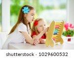 two cute little girls playing... | Shutterstock . vector #1029600532