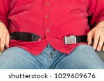 Small photo of Obese overweight passenger unable to fasten the seatbelt over his protruding belly sitting with it unclasped on an airplane in a close up cropped view