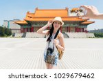 Small photo of Modern Asian teem taking photos in front of Chiang Kai-shek Memorial Hall. Joyfully standing like a model. Wearing short clothes. On a side view.