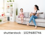 Small photo of Mom plays the wooden guitar daughter sing the songs. They have a warm family time over the weekend.