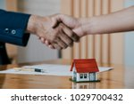 estate agent shaking hands with ...   Shutterstock . vector #1029700432