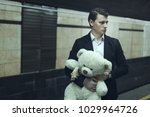 Small photo of Young man with a teddy bear, he worries before the meeting.