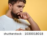 man with a beard holds a mug of ... | Shutterstock . vector #1030018018