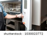 man operating offset machine... | Shutterstock . vector #1030023772