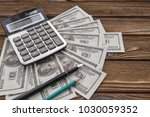 calculator on banknotes with a... | Shutterstock . vector #1030059352