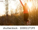photo from back jumping female... | Shutterstock . vector #1030117195