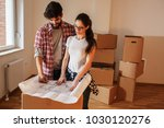 young couple moving into a new... | Shutterstock . vector #1030120276