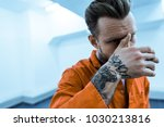 tattooed prisoner covering face ... | Shutterstock . vector #1030213816
