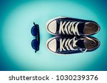 sneakers and glasses on a blue... | Shutterstock . vector #1030239376
