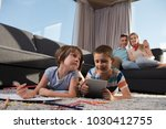 happy young family playing... | Shutterstock . vector #1030412755