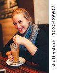a young girl drinks cappuccino... | Shutterstock . vector #1030439902