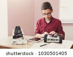 concentrated boy creating robot ... | Shutterstock . vector #1030501405