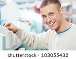 Smiling man at the pharmacy shelves - stock photo