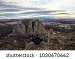 Small photo of Adventurous man sitting in a meditation position on top of a cliff during a vibrant sunset