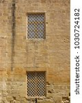 Small photo of Basic windows with grills against a ocher bricks wall