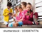 five kids are playing on phone... | Shutterstock . vector #1030874776