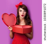 Small photo of Young brunet girl in red dress and bow with git box on purple background