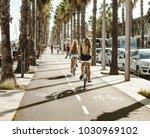 girls bike along the palm tree... | Shutterstock . vector #1030969102