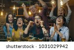 Stock photo diverse group of friends watches tv in the sporstbar beautiful young people drink have fun and 1031029942