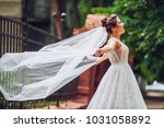 gorgeous bride looks up in the... | Shutterstock . vector #1031058892