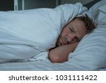 depressed man lying in his bed... | Shutterstock . vector #1031111422