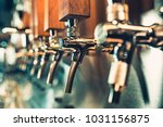 Stock photo the beer taps in a pub nobody selective focus alcohol concept vintage style beer craft bar 1031156875