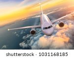 Commercial airplane jetliner flying above clouds in beautiful sunset light. Concept of travel and business. - stock photo