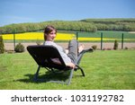 woman relaxing on a sun lounger ... | Shutterstock . vector #1031192782