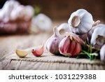 garlic cloves on rustic table.... | Shutterstock . vector #1031229388