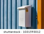 post box on blue wooden fence.... | Shutterstock . vector #1031593012