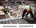 Concrete construction worker, pillar, steel rebar at construction site. Contractor worker works with concrete slab steel cage. Construction site with builder worker. Concrete slab construction. - stock photo