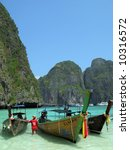Three traditional Thai boats in the Maya Bay of Phi-Phi island - stock photo