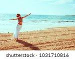girl walking on sand beach by... | Shutterstock . vector #1031710816