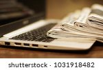Stock photo newspapers and computer laptop and daily papers on the table fresh news by paper or by 1031918482