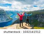 couple posing on trolltunga.... | Shutterstock . vector #1032161512