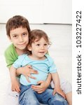 Brothers love - young boys sitting on the floor - stock photo