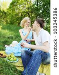 A woman feeding grapes to a picnic man - stock photo