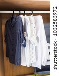 shirts hanging in wooden closet ... | Shutterstock . vector #1032583972