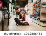 Stock photo father and dauther plays with puppy in pet shop 1032806458