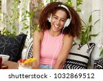 Small photo of Happy female with dark healthy skin, listens anecdotes online with special application and headphones, laughes at funny joke, sits on comfortable sofa against cozy cafe interior. People and spare time