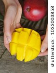 mango in female hands on wooden ... | Shutterstock . vector #1033003858