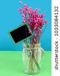 Small photo of Dried pink flowers in a hermetic jar on a blue and green background. Rustic slate message board in tucked into to arrangement, giving copy space for your message. Good for any gift giving special day.